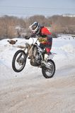Motocross rider on a motorcycle driving on winter road holding u Royalty Free Stock Images