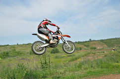 Motocross rider on a motorcycle in a jump. On a background of green on a clear day Stock Photo