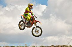 Motocross rider on a motorcycle spectacularly lands on a edge of. Motocross rider on a motorcycle is flying spectacularly in the last part of the flight Stock Photography