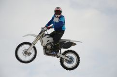 Motocross rider performs a high jump Stock Images