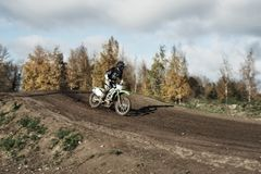 Motocross rider on race track. Motocross enduro rider in action accelerating the motorbike after the corner on dirt race track. Extreme off-road race. Hard Royalty Free Stock Photo