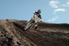 Motocross rider on race track. Motocross enduro rider in action accelerating the motorbike after the corner on dirt race track. Extreme off-road race. Hard Stock Photography