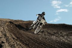 Motocross rider on race track. Motocross enduro rider in action accelerating the motorbike after the corner on dirt race track. Extreme off-road race. Hard Royalty Free Stock Photos