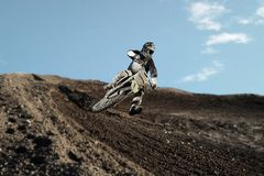 Motocross rider on race track. Motocross enduro rider in action accelerating the motorbike after the corner on dirt race track. Extreme off-road race. Hard Royalty Free Stock Photography