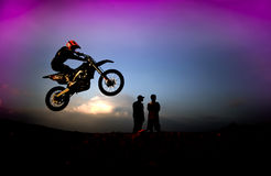 Motocross Rider in Silhouettes. The motocross racer jumping in the air while the team is watching closly Royalty Free Stock Photos