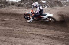 Motocross rider veering point-blank of sand with Stock Photos
