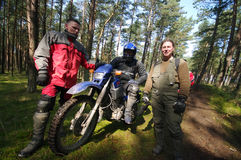 Motocross riders in forest. Three motocross riders in a forest. One of the is sitting on his motorbike (cross country type Royalty Free Stock Photography