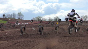 Motocross riders make a high leap into the air during a race stock footage