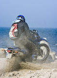 Motocross in sand. A motocross rider struggling with his bike in sand, sea (ocean) in the background stock photography