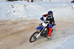 Motocross on snow racer on a motorcycle in the left turn having Royalty Free Stock Images