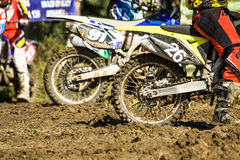 Motocross sport. Side view of two motocross motorcycles standing in mud royalty free stock image