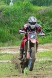 motocross Un motocycliste sur des précipitations d'une roue le long d'un chemin de terre, saleté vole de dessous les roues image stock