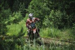 Motocrosschaufför på lerigt offroad spår Royaltyfria Bilder