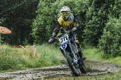 Motocrosschaufför på våt och lerig terräng Arkivfoton