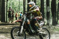 Motocrosschaufför på våt och lerig terräng Arkivfoto