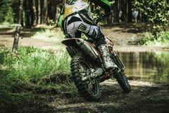 Motocrosschaufför på våt och lerig terrängsikt från baksidan Arkivbilder
