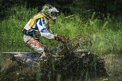 Motocrosschaufför under sprejen av gyttja Arkivfoton
