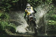 Motocrosschaufför under sprejen av vatten Arkivbilder