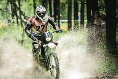 Motocrosschaufför under sprejen av vatten Arkivfoto