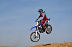Motocrossen motorcykelchaufför flyger över kullen ut ur snö Royaltyfria Bilder