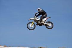 Motocrossen motorcykelchaufför flyger över kullen ut ur snö Royaltyfri Foto