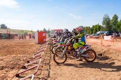 Motocrossers na raça de espera da linha de partida a começar Fotografia de Stock