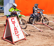 Motocrossers in the starting line waiting for race to start Royalty Free Stock Images