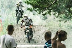 Motocrossfahrer auf nassem und schlammigem Gelände vom Berg Lizenzfreie Stockfotos