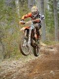 Motocrossfahrer, der mit dem Fahrrad an der hohen Geschwindigkeit auf der Rennstrecke springt stockfoto