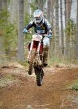 Motocrossfahrer, der mit dem Fahrrad an der hohen Geschwindigkeit auf der Rennstrecke springt lizenzfreie stockbilder