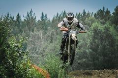 Motocrossfahrer springen über den Berg Lizenzfreie Stockfotografie