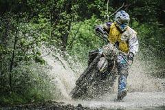 Motocrossfahrer unter dem Spray des Wassers Lizenzfreie Stockbilder