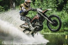 Motocrossfahrer unter dem Spray des Wassers Lizenzfreie Stockfotos