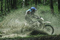 Motocrossfahrrad-Überfahrtnebenfluß, Wasserspritzen Lizenzfreie Stockbilder