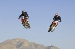 Motocrossracerbilar som utför jippo i Midair mot blå himmel royaltyfria bilder
