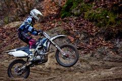 Motocrossreiter in der Aktion, die das Motorrad auf der Rennstrecke beschleunigt Lizenzfreie Stockbilder