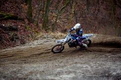 Motocrossreiter in der Aktion, die das Motorrad nach der Ecke auf der Rennstrecke beschleunigt Stockfotografie