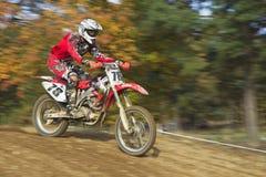 Motocrossrennläufer in rotem Identifikations-Reiten Stockbild