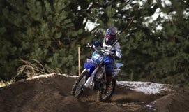 Motocrossruiter in actie die de motor na de hoek op het rasspoor versnellen Royalty-vrije Stock Fotografie
