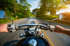 Motocycle. Driver riding motorcycle on an asphalt road through forest Stock Photos