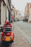 Motocycle rojo de la vespa parqueado en una calle en Bélgica fotografía de archivo