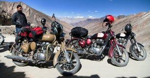 Motocycles brand Royal Enfield and biker. KHARDUNG LA PASS, LADAKH, INDIA, 11th SEPTEMBER 2013 - motocycles brand Royal Enfield and biker in highest road pass on Stock Photography