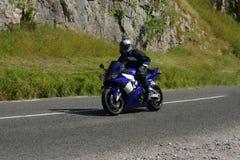 Motocyclette bleue, une main Images libres de droits
