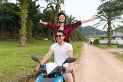 Motocyclette d'équitation de couples, jeune homme et voyage de femme sur le vélo sur Forest Road tropical Images libres de droits