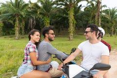 Motocyclette d'équitation de deux couples, jeune homme et voyage de femme sur le vélo sur Forest Road tropical Image libre de droits