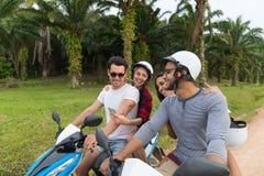 Motocyclette d'équitation de deux couples, jeune homme et voyage de femme sur le vélo sur Forest Road tropical Photos libres de droits