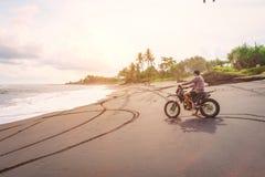 Motocyclette d'équitation Un homme monte son vélo de montagne sur une plage dans Bali Image stock