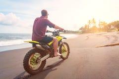 Motocyclette d'équitation Un homme monte son vélo de montagne sur une plage dans Bali Photographie stock libre de droits