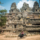 Motocyclette d'équitation de femme devant le vieux temple au complexe d'Angkor Vat Image stock