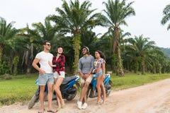 Motocyclette de deux couples, jeune homme et voyage se reposants de femme sur le vélo sur Forest Road tropical Photos stock